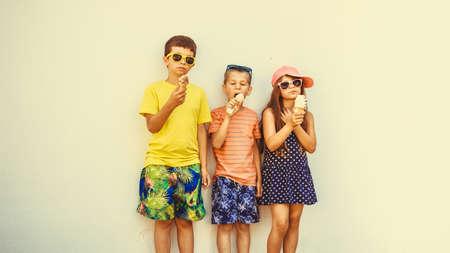 jovem: Crianças que comem gelato e sorvete. Meninos e menina em óculos de sol apreciam férias de verão férias. Filtro de Instagram.