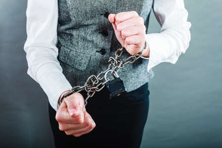 arrest: Crime, arrest jail or business concept. Closeup woman with chained hands on grunge background