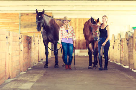 Westerse cowgirl en jonge vrouw lopen met paarden in stabiele paddock. Instagram filter.