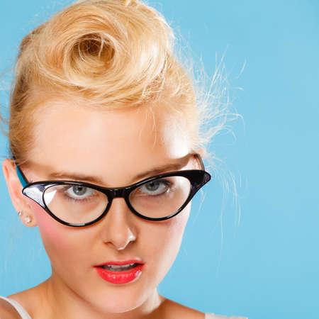 oculista: Optometrista, oculista y el concepto oftalmólogo. Joven rubia retro pin up mujer con gafas en el fondo azul en el estudio. Foto de archivo