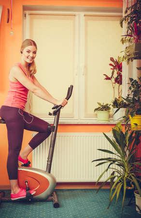 ecoute active: Actif jeune femme travaillant sur un v�lo d'exercice v�lo stationnaire. La formation de fille sportive � la musique d'�coute � domicile. Fitness et le concept de perte de poids.