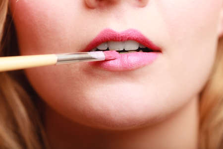 makeover: Cosmetic beauty procedures and makeover concept. Closeup part of woman face pink lips. Make-up artist applying lipstick with accessories tools.