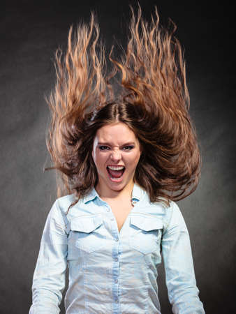Happy and ecstatic woman having fun. Carefree young girl with long hair in motion. Wind. Stock Photo