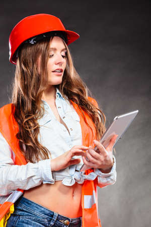 alluring: Sexy alluring woman structural engineer wearing helmet holding tablet computer. Strong girl feminist working in man profession. Independent female.