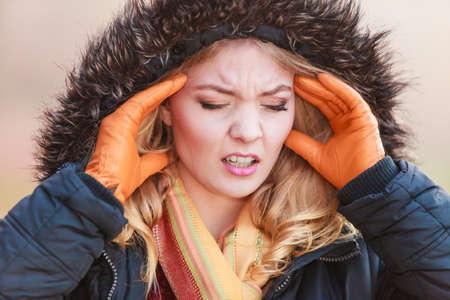 gripe: Retrato de la mujer bastante de moda que sufren de dolor de cabeza. Chica joven en la chaqueta con capucha llamó virus de la gripe frío. La caída del otoño de la moda de invierno. Foto de archivo