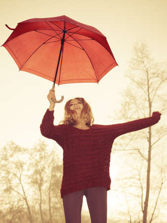 woman sweater: Happy fashion cute woman girl in maroon sweater with umbrella relaxing in foggy hazy fall autumn park. Happiness and relax in forest.
