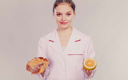 eating right: Dietitian nutritionist with sweet roll bun and grapefruit. Woman holding fruit and cake comparing junk and healthy food. Right eating nutrition concept.