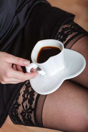 Sexy female legs in stockings and heart shaped cup of coffee, unusual high angle view