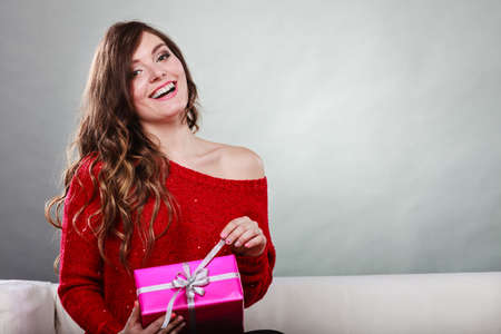 People celebrating xmas love and happiness concept - beauty girl opening present pink gift box sitting on sofa at home