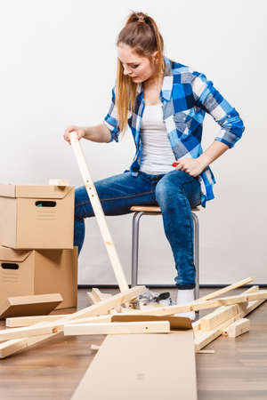 unpacking: Woman moving into new apartment house assembling furniture using scredriver. Young girl arranging interior and unpacking boxes. DIY. Stock Photo