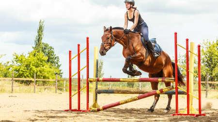 salto de valla: Entrenamiento jinete Mujer equitaci�n saltar sobre la cerca. Competici�n deporte ecuestre.