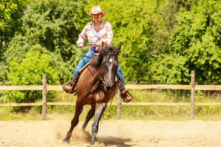 Active western cowgirl woman in hat training riding horse. American girl in countryside ranch. Horseback sport activity. Stock Photo