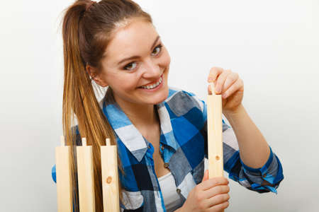 self assembly: Woman assembling wooden furniture using screwdriver. DIY enthusiast. Young girl doing home improvement.