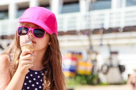 serve: Kid eating gelato soft serve ice cream. Little girl in sunglasses enjoying summer outdoor.
