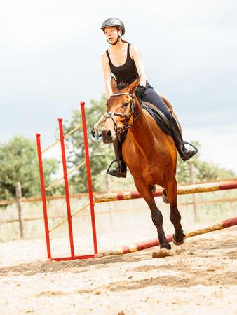 salto de valla: Activo equitación formación jinete muchacha mujer saltando sobre la cerca. competición deporte ecuestre y actividad.