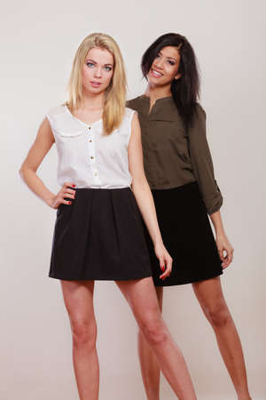 skirts: Two young women caucasian and african in trendy short black skirts posing studio portrait on gray Stock Photo