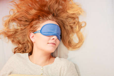 Tired woman sleeping in bed wearing blindfold sleep mask. Young girl taking nap.