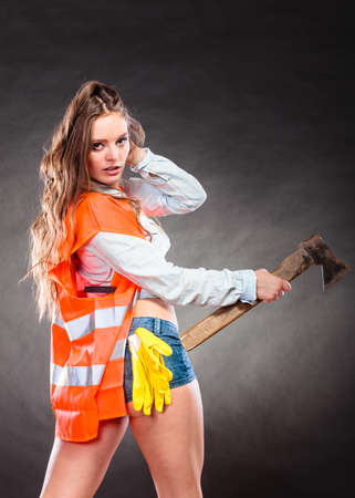 feministische: Sexy alluring woman wearing helmet and safety workwear holding axe chopper. Strong girl feminist working in man profession. Independent female. Stockfoto