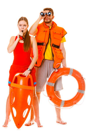 Lifeguards with rescue tube ring buoy lifebuoy and life vest jacket looking through binoculars. Man and woman supervising swimming pool whistling. Accident prevention.