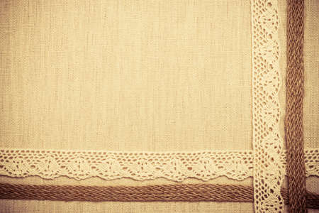 bagging: Lace frame on natural linen, bright cloth fabric background. Retro vintage style Stock Photo