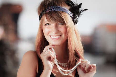 twenties: Flapper girl portrait. Retro style fashion vintage woman from roaring 1920s in headband with string of pearls, outdoor. City background Stock Photo