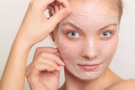 cosmeticos: Belleza cosméticos cuidado de la piel y el concepto de salud. Primer rostro de mujer joven, muchacha que quita facial mascarilla exfoliante en gris. Descamación Foto de archivo