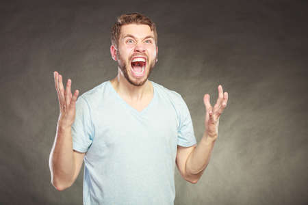 man yelling: Angry man yelling . Hands are raised in air. Bad emotion face expression.