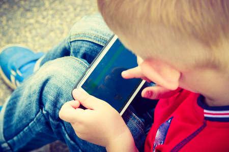 Little Kid enfant garçon jouer à des jeux sur téléphone intelligent téléphone mobile en plein air. la génération de la technologie. Banque d'images