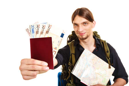 spendthrift: Man tourist backpacker holding map and passport full of money. Young guy hiker backpacking. Summer vacation travel. Studio shot. Isolated on white background.
