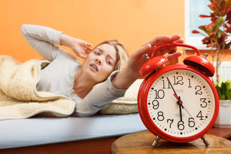 turning off: Exhausted woman waking up in bed turning off alarm clock. Young girl in the morning. Stock Photo