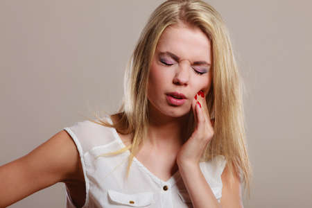 mouth pain: Dental care and toothache. Closeup young woman face worried girl suffering from tooth pain on gray