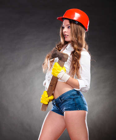 feministische: Sexy alluring woman wearing helmet holding axe chopper. Strong girl feminist working in man profession. Independent female.