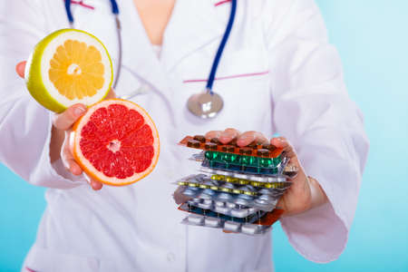 medical choice: Health and balanced diet concept. Choice between two sources of vitamins - pills or fruits. Medical doctor offering chemical and natural vitamins, holding stack of drugs and grapefruits on blue.