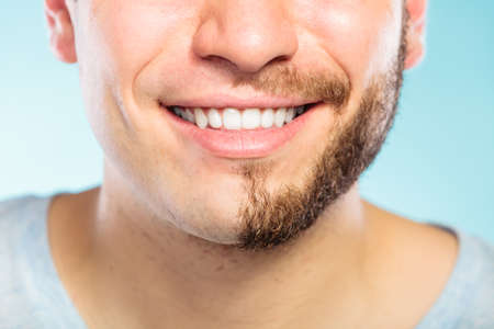 Closeup of happy man with half shaved face beard hair. Smiling guy on blue. Skin care and hygiene.