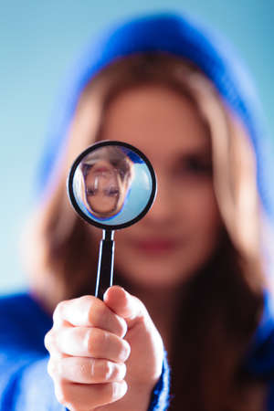 lupa: Investigation exploration education concept. Woman teen girl looking through a magnifying glass loupe on blue Stock Photo
