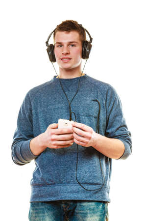 cool gadget: Teenage and technology concept. Young man casual style with headphones smartphone listening music isolated on white