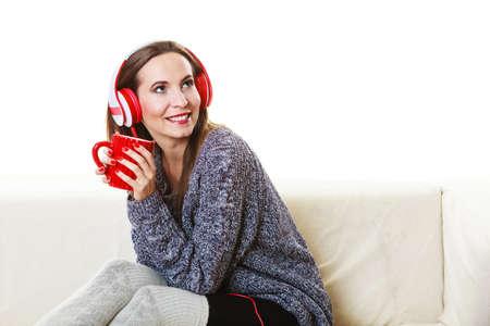 relajado: Gente ocio relajarse concepto. Mujer del estilo ocasional rojos grandes auriculares escuchando música mp3, sentado en el sofá en casa de relax beber café té caliente