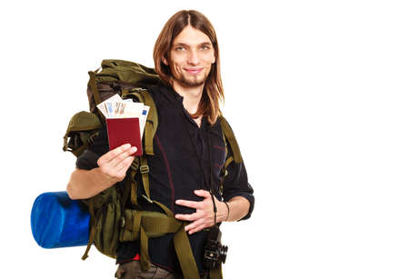 spendthrift: Man tourist backpacker holding passport full of money. Young guy hiker backpacking. Summer vacation travel. Studio shot. Isolated on white background.