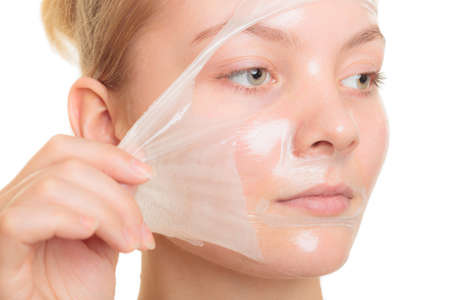 Beauty skin care cosmetics and health concept. Closeup young woman face, girl removing facial peel off mask isolated on white. Peeling Standard-Bild