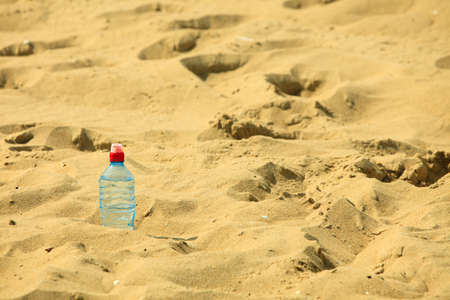 thirst: thirst and bevarage. closeup of plastic bottle of water drink on a sandy summer beach. vacation fitness