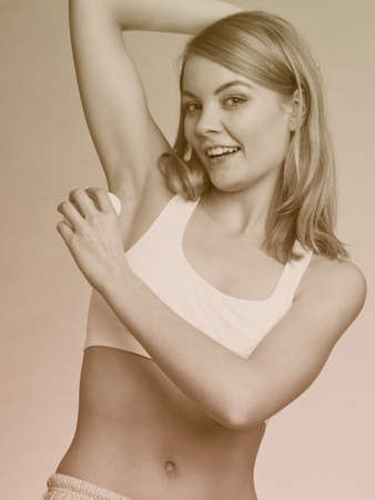 underarms: Daily skin care and hygiene. Girl applying stick deodorant in armpit. Young woman putting antiperspirant in underarms sepia tone