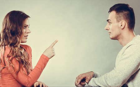 couple talking: Couple talking on date. Woman warning man. Boyfriend and girlfriend having conversation. Girl threatening with finger.