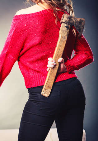 sneaky: Sneaky woman holding axe. False intention. Young girl hiding chopper, axe. Back, rear view. Stock Photo