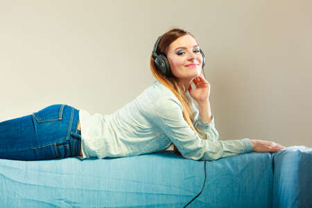 relaxation: People leisure relax concept. Lovely woman big headphones listening music mp3 relaxing on couch