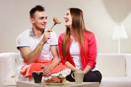 caloric: Smiling man feeding happy woman with cake. Wife and husband eating caloric food.
