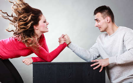 wrestle: Partnership relationship concept. Girlfriend confronts his boyfriend. Woman and man arm wrestling challenge between young couple