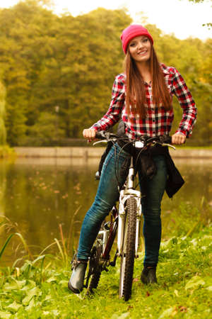 active lifestyle: Fall active lifestyle concept,. young woman sporty casual girl relaxing in autumnal park with bicycle, outdoor