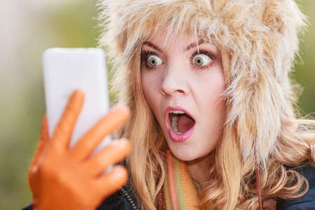 Portrait of scared afraid pretty woman talking on mobile phone. Gorgeous young girl in fur winter hat and jacket. Autumn fashion and communication.