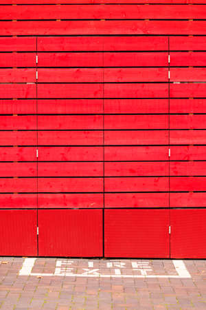 fire exit sign: Old red wooden panels as background or texture. Fire exit sign.