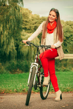 woman fashionable: Fall active lifestyle concept,. Beauty young woman fashionable girl relaxing in autumnal park with bicycle, outdoor